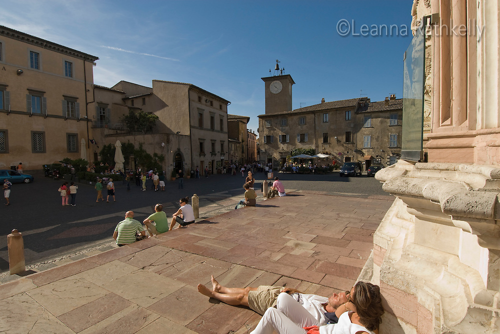 People relax in the sun on the steps of the basilica, set in the central piazza in the town of Orvieto, Italy.