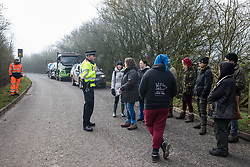 Denham, UK. 6 February, 2020. A police officer speaks to environmental activists from Save the Colne Valley, Stop HS2 and Extinction Rebellion walking at a snail's pace along a road to block a security vehicle and truck delivering fencing and other supplies to be used for works associated with the HS2 high-speed rail link close to the river Colne at Denham Ford. Works planned in the immediate vicinity include the felling of trees and the construction of a Bailey bridge, compounds and fencing, some of which in a wetland nature reserve forming part of a Site of Metropolitan Importance for Nature Conservation (SMI).