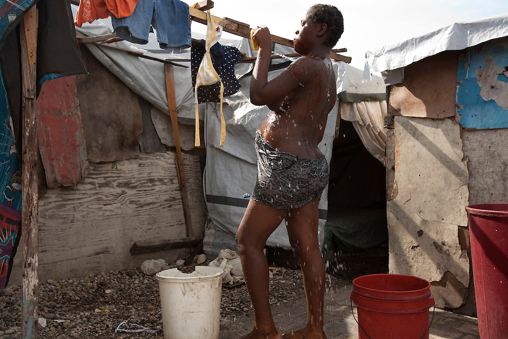 Ema Yanick, 16 years-old,who is pregnant and taking care of her two brothers, her 2 brothers Giovanni, 7 year- old, Junior,13 year-old, after losing her parents in the Haiti earthquake, in the makeshift refugee camp, La Piste, in Port-au-Prince, Haiti on July 18, 2010. <br />  La Piste (French for &quot;runway&quot;)is a settlement sprawled across the site of a disused airport and now home to an estimated 20,000 earthquake survivors living in makeshift structures.<br /> Six month after a catastrophic earthquake measuring 7.3 on the Richter scale hit Haiti on January 13, 2010, killing an estimated 230,000 people, injuring an estimated 300,000 and making homeless an estimated 1,000,000.