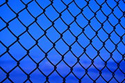 Section of Cyclone Fencing against blue twilight sky abstract