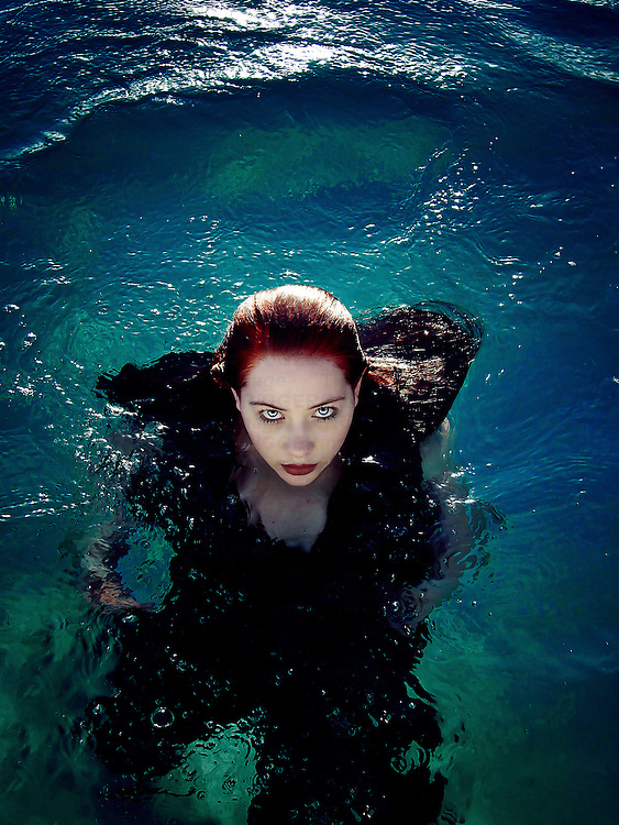 Young woman with red hair and a flowing black dress floating in dark blue and green water, staring ominously into the camera