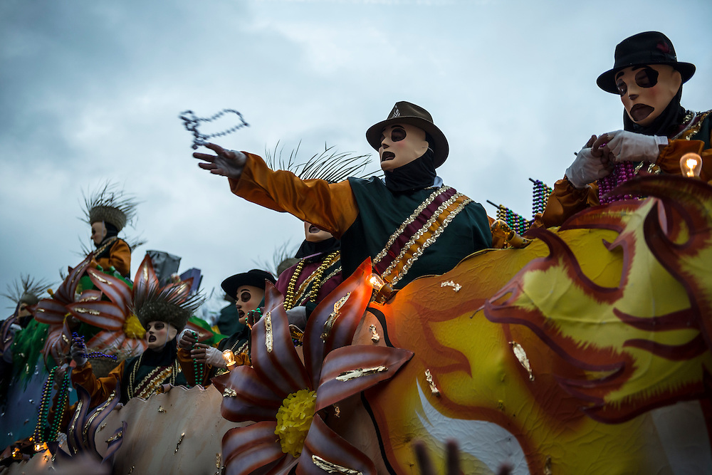 A costumed man throws beads toward the crowd during a Mardi Gras parade on Canal Street in New Orleans, Louisiana.