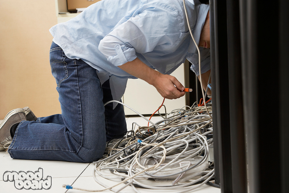 Man working on tangle of computer wires in office
