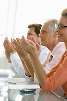 Business colleagues applauding in conference meeting