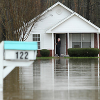 A Saltillo residents stands on his front porch whith his home surrounded by flood waters in the Willow Creek subdivision on Friday afternoon.
