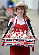 © Licensed to London News Pictures. 01/06/2012. Epsom , UK A young woman sells strawberries and cream. Ladies Day today 1st June 2012 at Epsom 2012 Investic Derby Festival. The Queen will attend tomorrow's race meet as part of the 60th Jubilee celebrations. Photo credit : Stephen Simpson/LNP