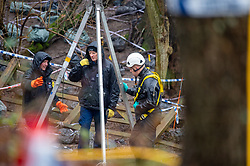 © Licensed to London News Pictures. 17/12/2019. Beaconsfield, UK. A member of a search team wearing a dry suit and a harness talks with colleagues at an ingress point to what appears to be an underground area. London's Metropolitan Police Service have called in the forces specialist Under Water and Confined Space Search Team as they continue to search woodland in Beaconsfield. The Met confirmed on 12th December 2019 they are searching the woodland in Beaconsfield, Buckinghamshire in connection with the disappearance and murder of Mohammed Shah Subhani. Police have been in the area conducting operations on Hedgerley Lane since Thursday 5th December 2019 and are combing wooded area with specialist officers assisted by specialist search dogs. Photo credit: Peter Manning/LNP
