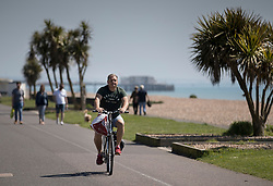 © Licensed to London News Pictures. 05/05/2018. Worthing, UK. A cyclist on the sea front at Worthing soaks up the sunshine. Record temperatures are expected this bank holiday weekend. Photo credit: Peter Macdiarmid/LNP