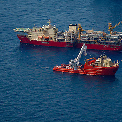 Helix Energy Solutions Group's Helix Producer I (top) vessel is in the process of being connected to the well at the source of the BP Plc Deep Water Horizon oil spill site in the Gulf of Mexico off the coast of Louisiana, U.S., on Sunday, July 11, 2010. The Helix Producer I once connected at the well site will be capable of storing up to 30,000 additional barrels per day from the well gushing at the bottom of the Gulf of Mexico. Photographer: Derick E. Hingle/Bloomberg