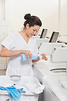 Happy young female employee pouring detergent in washing machine Laundromat