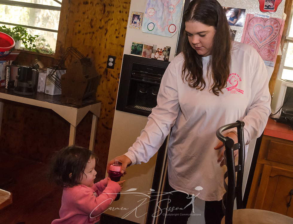 Former day care worker Sara Morales gives a bottle of juice to her daughter, 18-month-old Carleigh Morales, March 4, 2016, at her home in Loxley, Alabama. Morales worked briefly for day care owner Deborah Stokes at A Step Ahead Christian Day Care but says she quit because Stokes yelled at the children and failed to pay her. Morales now babysits children at her home, and Stokes has opened a new day care, Little Nemo's, in Spanish Fort, Alabama. (Photo by Carmen K. Sisson/Cloudybright)