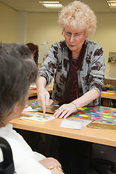 Volunteer assisting in craft activity at a resource for people with physical and sensory impairment.