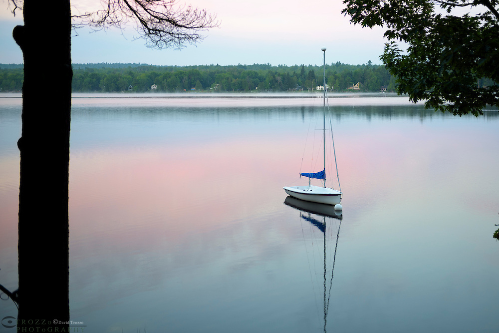 Sailboat moored on Toddy Pond at sunrise, Orland, Maine.