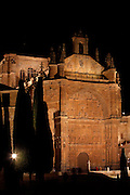 """Low angle view of Convent of St. Stephen, Salamanca, Spain, pictured on December 19, 2010 at night, floodlit. Commissioned by order Juan Alvarez de Toledo, Bishop of Cordoba, and designed by Juan de Alava, the church was built 1525-1618. The main portal, c.1660, has a row of decorated arches and a tympanum with a relief of the """"Martyrdom of St. Stephen"""", by Juan Antonio Ceroni. Above it is a frieze in Italian style, depicting Calvary crowned by the Eternal Father. Salamanca, an important Spanish University city, is known as La Ciudad Dorada (""""The golden city"""") because of the unique golden colour of its Renaissance sandstone buildings. Founded in 1218 its University is still one of the most important in Spain. Around it the Old Town is a UNESCO World Heritage Site. Picture by Manuel Cohen"""