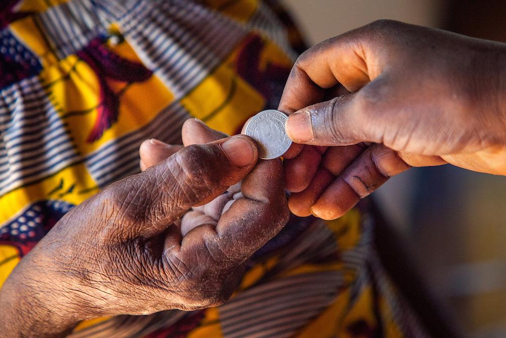 LÉGENDE: La femme perçoit l'argent d'un client pour moudre les noix de Karité. LIEU: Centre COFEMAK, Koumra, Tchad. PERSONNE(S): Main de la Femme (à gauche) et main du client (à droite).