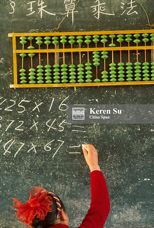 Girl student studying Chinese abacus at chalkboard, Anhui Province, China