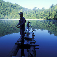 Canada, British Columbia, Alice Lake Provincial Park, (MR) Ross Miller fishes with son Dustin on floating log at dawn