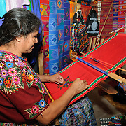 A Maya woman using a backstrap loom to weave a Christmas-themed decorative textile in a market stall in Antigua, Guatemala.