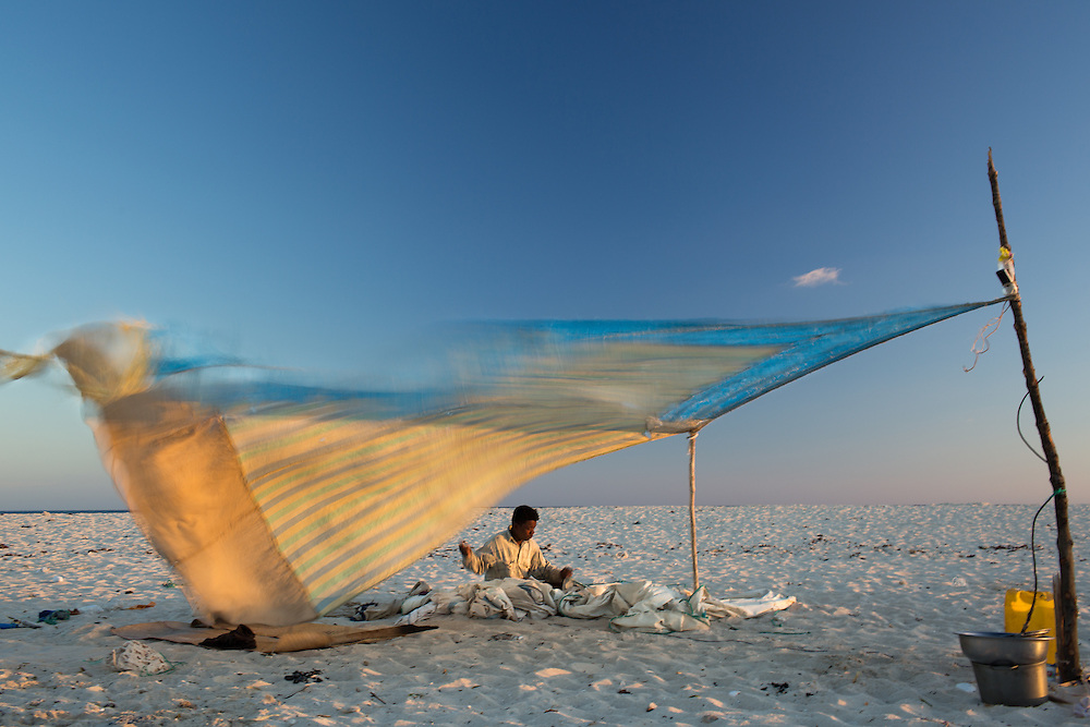 A traditional migrant fisherman repairs his sail in preparation for the next day's fishing trip.  Fishers live on tiny offshore islands and sand cays so that they are able to access remote fishing grounds in the Mozambique channel.  On the sand cays there is no shade; so during the heat of the day, they often use their sails to shelter from the sun.