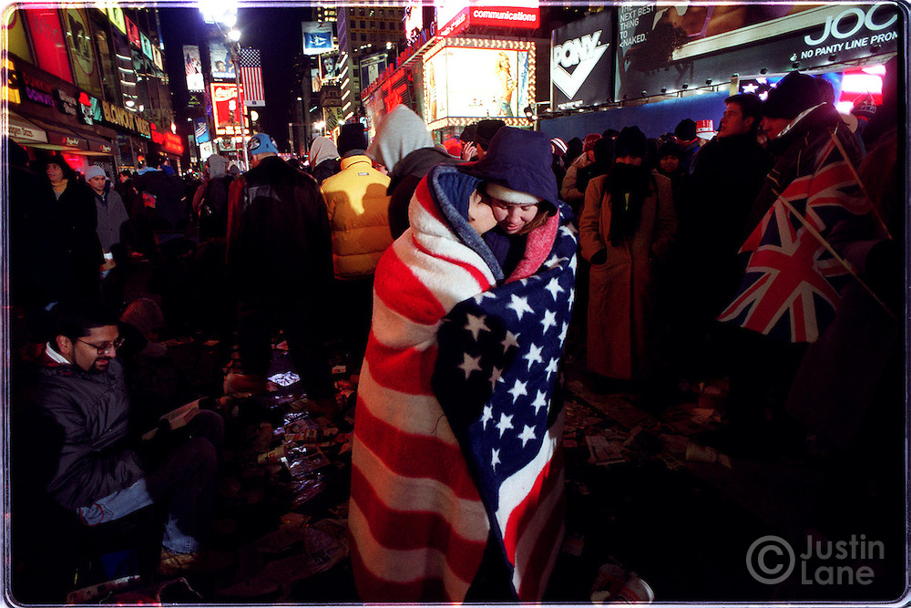 NYEVE4/8   Photographs in Times Square of New Year's Eve Revelers. They are:Bobby Chatterjee, 9, and his mother Marge, are seen wrapped up in an American flag blanket. They are from Redding, CT.   Justin Lane for The New York Times       --Original IPTC Information:   Caption: Photographs in Times Square of  New Year's Eve Revelers. they are:  Jack Speers, of Austin, TX, in 2002 glasses smoking a cigar. with him is Amanda Kelly, of Pittsburgh, PA, at right.  Carmela and Josh Combs of san Jose, CA who were just married today in Manhattan's City Hall and then came to times Square (Carmela has a bridal viel on her head)  A group of guys waving a flag around: justin McCarthy, with hat, Jay Wehrenberg, with black leather jacket, Pete Solook, w/ 2002 glasses, and Amy Cotese. All are from Clinton, NJ  Jason Bradfield and Laura Carpenter, of Clinton, NJ, seen lying in a chair amongst the crowd in the middle of Times Square. in some frames they are kissing.  Bobby Chatterjee, 9, and his mother Marge, seen wrapped up in an American flag blanket. they are from Redding, CT.       Credit:  the New York Times    Source:  the New York Times    Province-State:  Changed from no prior entry.    Country Name:  Changed from no prior entry.    Original Transmission Reference:  Changed from no prior entry.