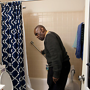 Caretaker Reggie Griffin checks out the grab bar in Mr. Johnson's bathroom. John E. Johnson, who is not eligible for medicaid, receives services for 12 hours per week through Illinois' Community Care Program. Johnson worries his services will be cut if the state transition seniors like him to a new program. The state employs Reggie Griffin to help Johnson with daily chores so he is able to stay in his home, as opposed to going to an nursing home. <br /> Photography by Jose More