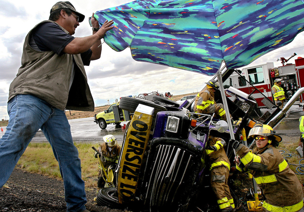 Xavier Mascareñas/The Daily Times; Passerby Sam Martinez, of Aztec, N.M., collects his umbrella from a firefighter on June 24, 2009, after using it to help shield semitrailer driver Jorge Ayala from rain after an accident on southbound U.S. 550 outside Bloomfield.  Ayala was transported to San Juan Regional Medical Center with minor injuries.
