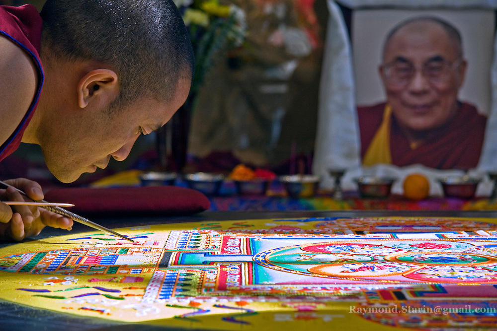 Lobsang Tsering a monk from the Drepung Loseling Monastery in Tibet surgically works on a Mandala sand painting in the Hearth Room of the student union.