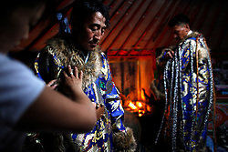 Mongolian Shaman brothers Gankhuyag (C) and Batgerel Batmunkh (R) dress up in their Shaman  costumes with their sister, Munkhzul's help before performing a Shaman healing ritual in their ger on the outskirts of Ulan Bator, Mongolia, 04 July 2012. Mongolian brothers Gankhuyag and Batgerel Batmunkh share a similar fate. Both were construction workers before fate calls on them to take on their Shamanic roles to serve the spirits. Shamanism comes from the term 'shamans' that refers to priests or mediums that acts as vessels for spirits, gods and demons to communicate with the human world. In Mongolia, they adhere to the ancient beliefs of Tengrism, where spirits live in all of nature, in the sun, moon, lakes, rivers, mountains, and trees.