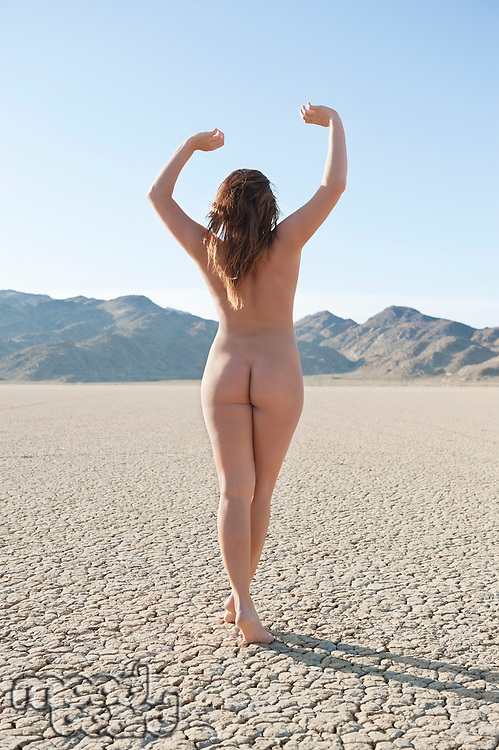 Back view of naked woman walking on barren landscape with hands raised