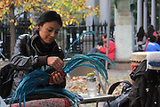 New York, New York. November 1, 2013. Yadira Aleman, 33,  prepares her headdress. Three members of her dance group, Kalpulli Atl-Tlachinolli performed at a Dia De Los Muertos celebration outside St. Mark's Church in the Bowery. 11012013. Photo by Maya Rajamani/NYCity Photo Wire
