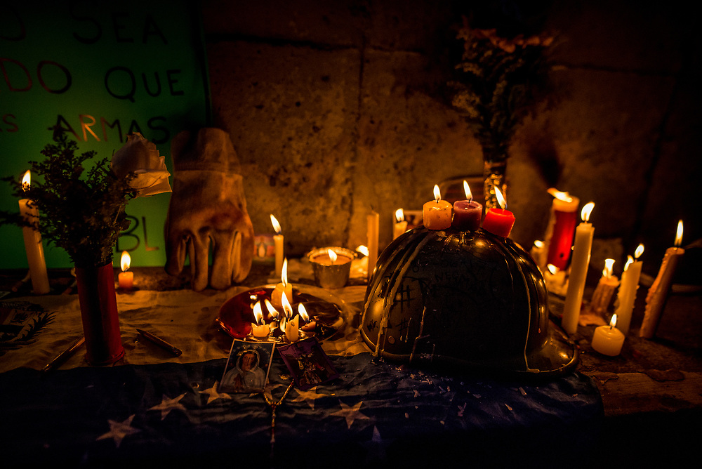 """CARACAS, VENEZUELA - JUNE 8, 2017: Members of """"The Resistance"""" light candles and construct a makeshift memorial around the blood-stained spot on the road where anti-government protester Neomar Lander, 17, was killed by security forces during a protest in Caracas. Johan Caldera, a close friend of Mr. Lander said he is even more determined to protest since his friend was killed.  """"Now, I have no fear - because I already lost the fear I had, and the respect for the military. The little respect I had, is gone. Now, the real soldiers of Venezuela wear rags on their faces, they wear a glove and they they don't use grenades - they use stones, they use their will, and they use their balls to go out into the street."""" He said he had discussed with Neomar the possibility of being killed during the protests, """"and he [Neomar] told me: brother, if I die - if I lose my life during a protest, I don't want everyone to stop marching, I want them to march double and keep going to the street for a week, every single day, day and night without fear.""""  PHOTO: Meridith Kohut"""