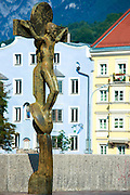 Statue of Christ and traditional Tyrolean ornate architecture by the River Inn in Innsbruck in the Tyrol, Austria