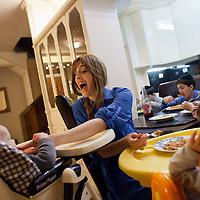 Miri Beillin, an ultra orthodox Jewish stylist and fashion designer, feeds her children during dinner at their house in Bnei Brak