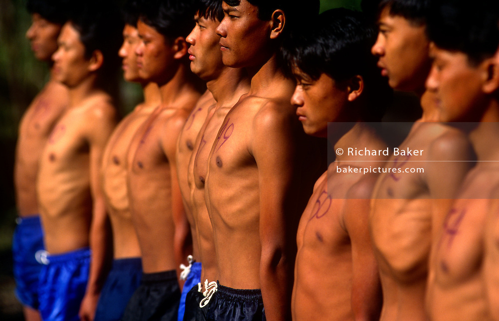 Young Nepali boys attend a line-up in Himalayas, hoping to be recruited for the Gurkha Regiment in the Btitish army. .This is part of a tough endurance series to find physically perfect specimens for British army infantry training. For example, they will need to perform 25 straight-kneed sit-ups at a 45° slant both within 60 seconds to pass. 60,000 boys aged between 17-22 (or 25 for those educated enough to become clerks or communications specialists) report to designated recruiting stations in the hills each November, most living from altitudes ranging from 4,000-12,000 feet. After initial selection, 7,000 are accepted for further tests from which 700 are sent down here to Pokhara in the shadow of the Himalayas. Only 160 of the best boys succeed in the journey to the UK. The Gurkhas have been supplying youth for the British army since the Indian Mutiny of 1857.