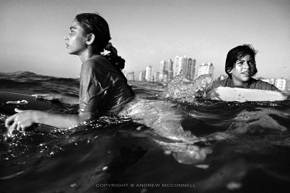 Sabah Abo Ghanem, 11, and Kholoud Abo Ghanem, 10, look to the horizon while bodyboarding off Gaza City, Gaza Strip. The girls are cousins and along with their two sisters they represent the only female surfers in Gaza. The girls practise surfing when they can borrow surfboards but lack their own, as these are few and far between in Gaza.