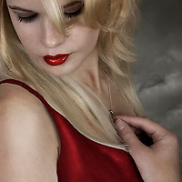 blonde young woman wearing red dress and necklace looking down