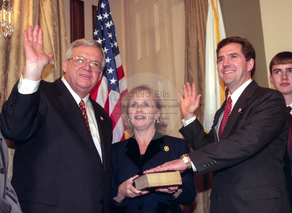 Speaker of the House Denis Hastert (L) administers the oath of office to Rep. Jim DeMint of South Carolina as his wife Debbie and family looks on January 6, 1999 at the start of the 106th Congress. The oath is a recreation as the formal oath is administered to the entire congress as a body on the floor of the House.