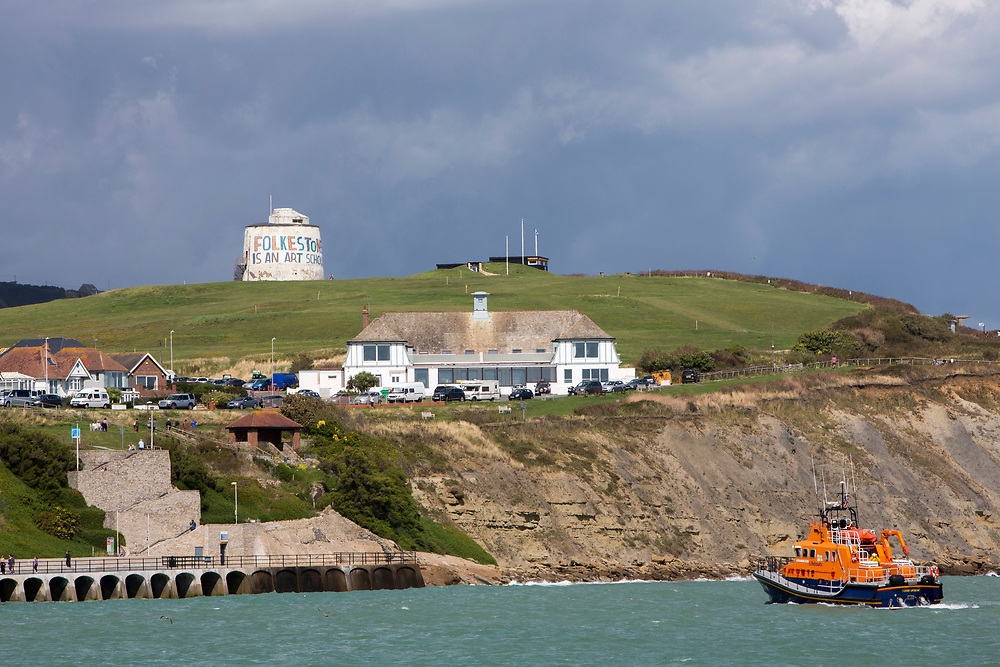 The Royal National Lifeboat Institution RNLI Dover Life boat (17-09)  arrives into Folkestone near the Folkestone is an Art School banner, attached to Folkestone's most prominent Martello Tower on the east cliff. The banner has been designed by the artist Bob and Roberta Smith as part of the 2017 Folkestone Triennial. Folkestone, Kent.(photo by Andrew Aitchison / In pictures via Getty Images)