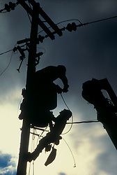 Stock photo of a silhouette of two men working on a power pole in the afternoon