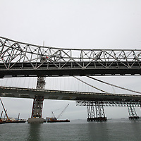 The San Francisco-Oakland Bay Bridge is under construction, and scheduled to open Labor Day 2013. The Self-Anchored Suspension Span (SAS) is the largest bridge of its kind in the world measuring 2,047 feet. This engineering and construction marvel raises the bridge building bar to new heights, as seen in these behind the scenes photos taken on Monday, March 18, 2013. This images shows the currently used, original bridge in the foreground, with the new spans in the rear. (AP Photo/Alex Menendez)