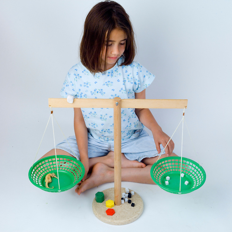 Measurment using pan balance series.  Girl weighing objects using a pan balance.