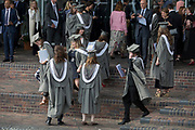 Young graduates wearing rented gowns and mortarboards have photos taken by family members after their university graduation ceremony, on 13th July 2017, at the University of York, England.