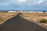 Cyclist on road approaching Caleta de Caballo village, Lanzarote, Canary islands, Spain