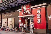 People wait outside a Kentucky Fried Chicken fast food restaurant along Wangfujing Street in Beijing, China