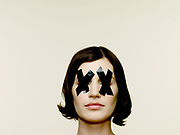 Portrait of woman with black electrical tape over eyes.