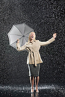 Woman standing in overcoat holding umbrella singing in the rain