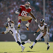 San Francisco 49er Vernon Davis leaps over St. Louis Rams Rodney McLeod and St. Louis Rams James Laurinaitis after a pass reception at Candlestick Park in San Francisco, California.