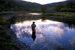Stock photo of fisherman flyfishing on the Upper Yampa river outside of Steamboat Springs, Colorado at sunset.