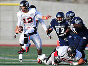 Image © 2013, Darin Sicurello/ Sports Shooter Academy || Yorba Linda, California November 16, 2013 Quarterback Shane Truelove of Santa Ana College runs for yardage against Defensive Linesmen Antoine Turner and Aaron Davis of Fullerton College during the final game of the season
