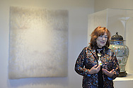 Roslyn, New York, USA. January 2, 2015. LINDA SCHWARTZ, a docent shares information about the artwork exhibits at the Nassau County Museum of Art China Now and Then Exhibit on Long Island. Artwork on wall by Chinese artist Lin Tianmiao is Digital Photograph on canvas with thread, with eyes nose and lips of face faintly visible.